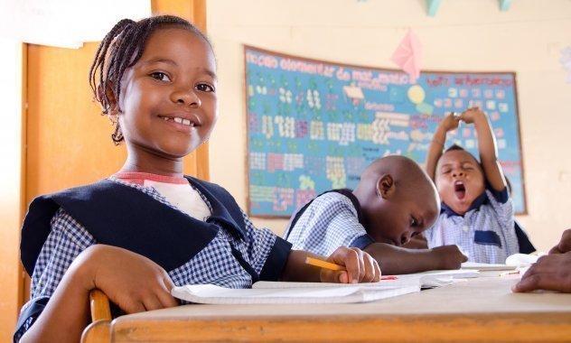 Kleines Mädchen in Schuluniform in der Schule, lachend.