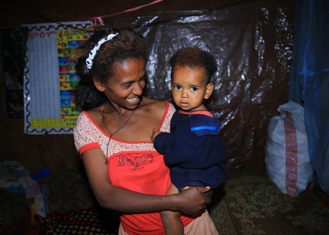 Mutter hält afrikanisches Kind im Arm und lächelt.