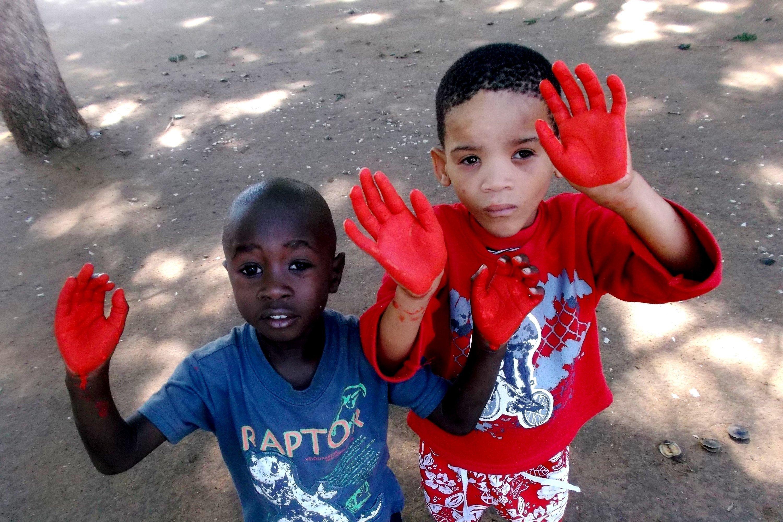 Mit rotgefärbten Händen setzen die Kinder in Namibia ein Zeichen gegen Kindersoldaten!
