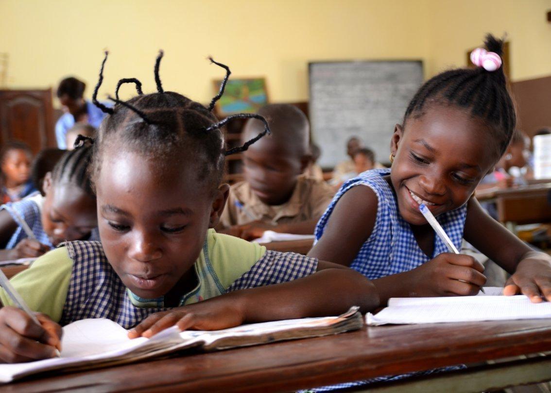 Zwei kleine Mädchen schreiben in der Schule.