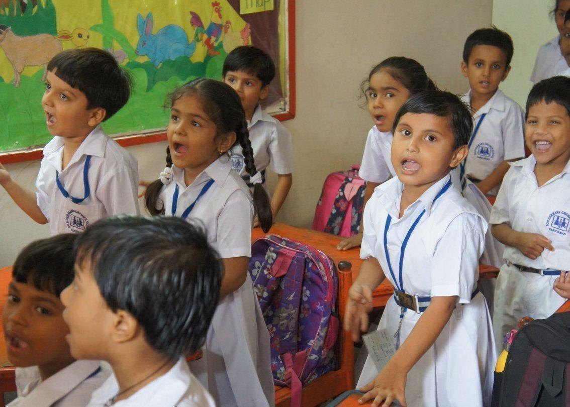 Kinder in Schuluniform singen ein Lied zusammen.