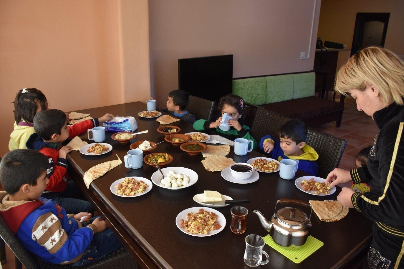 SOS-Kinderdorf Mutter sitzt mit Kindern beim Essen am Tisch.