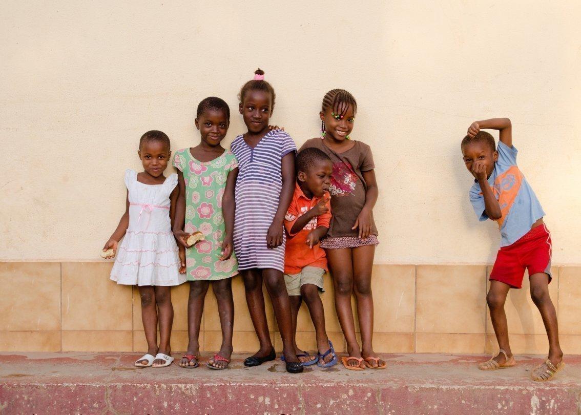 Kleine Kinder stehen vor einer Hauswand und lachen.