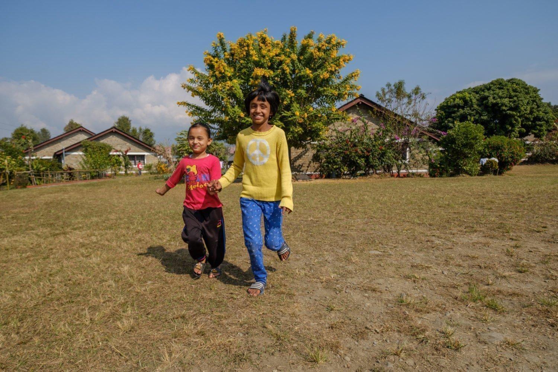 zwei Kinder laufen Händchen haltend über eine Wiese.
