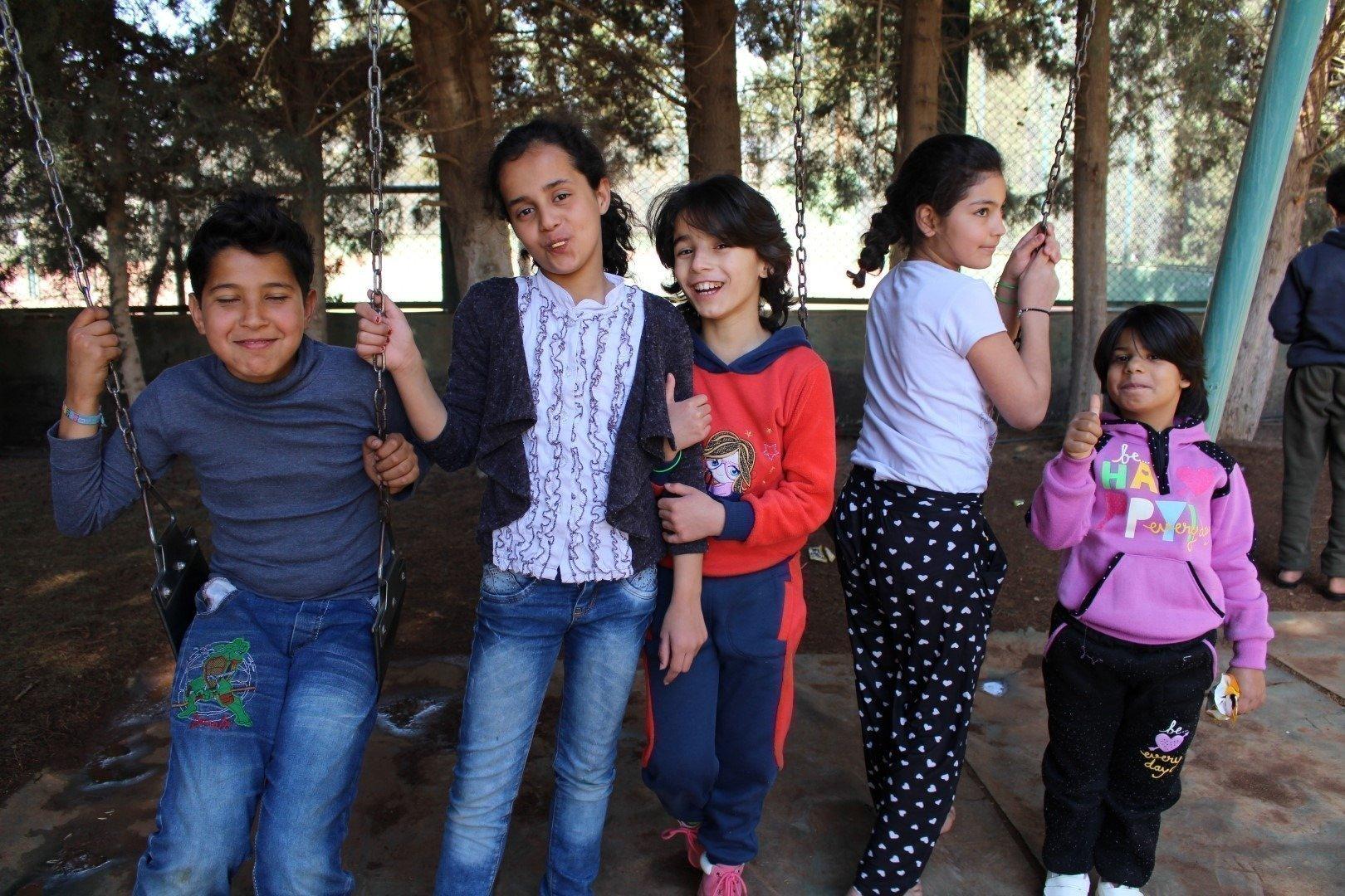 Gruppe von Kindern an Schaukeln.