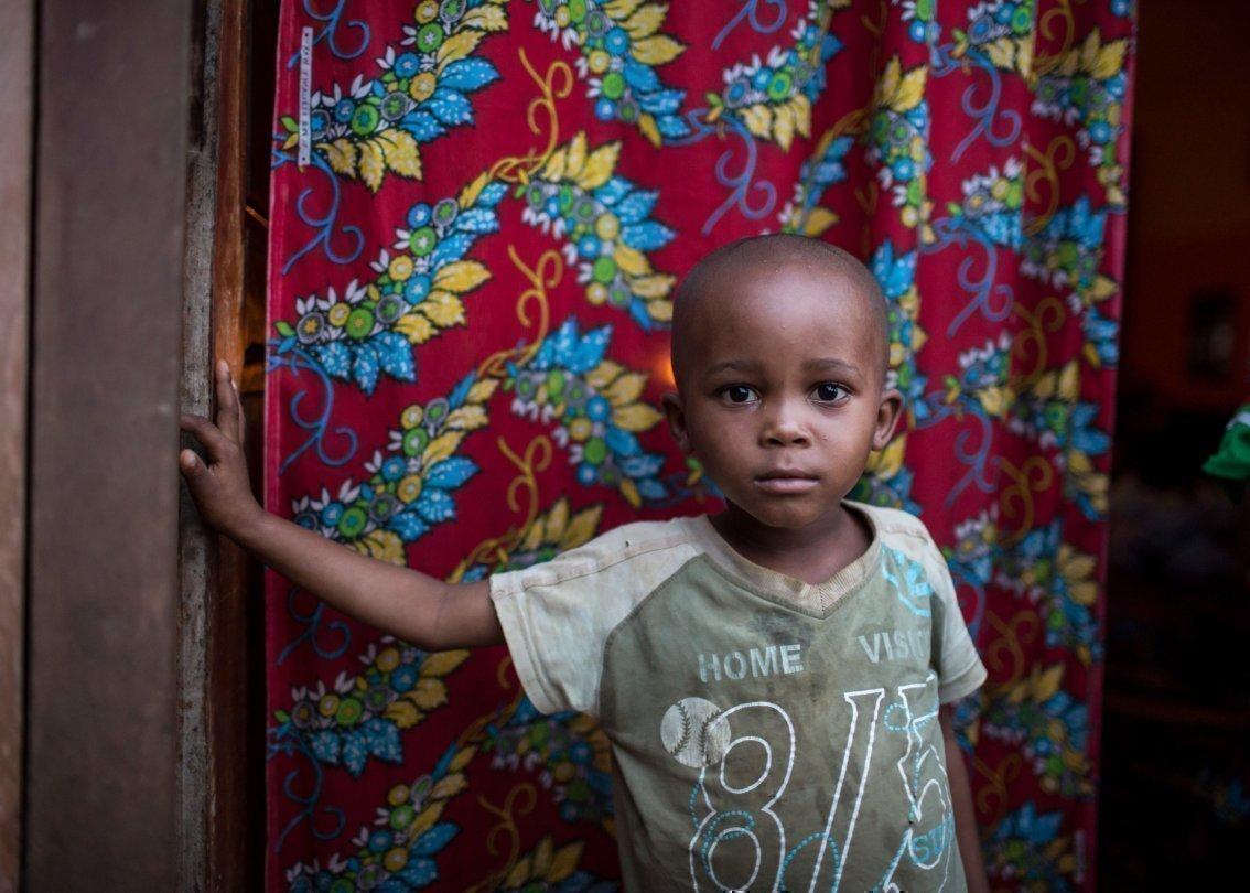 Ein kleiner Junge steht vor einem bunten Teppich und schaut in die Kamera.