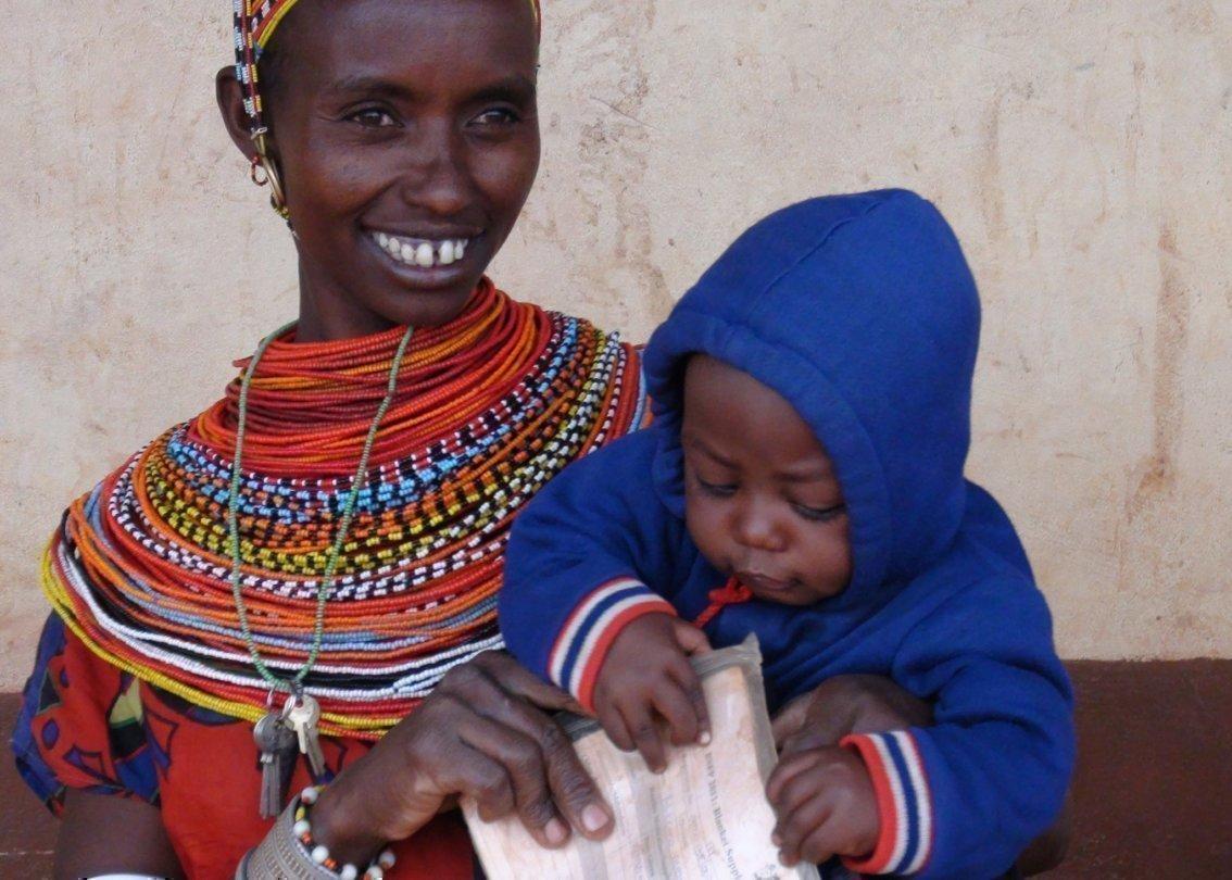Lächelnde Frau mit Baby auf dem Arm.