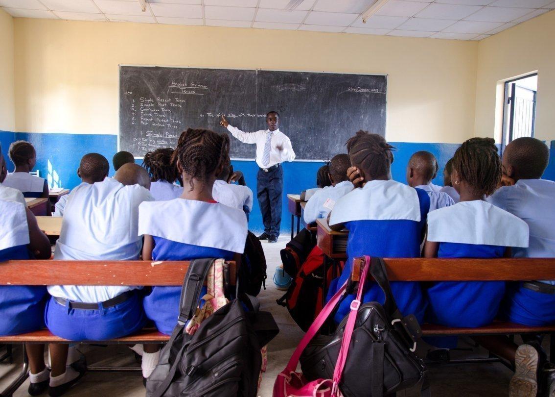 Mehrere Kinder in Uniform sitzen auf Schulbänken und hören ihrem Lehrer zu.