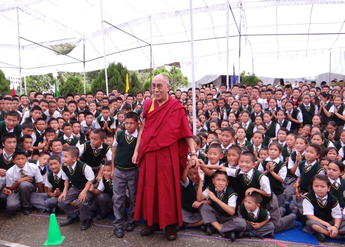 Dalai Lama steht vor hunderten von SOS-Kinderdorf Schülern.