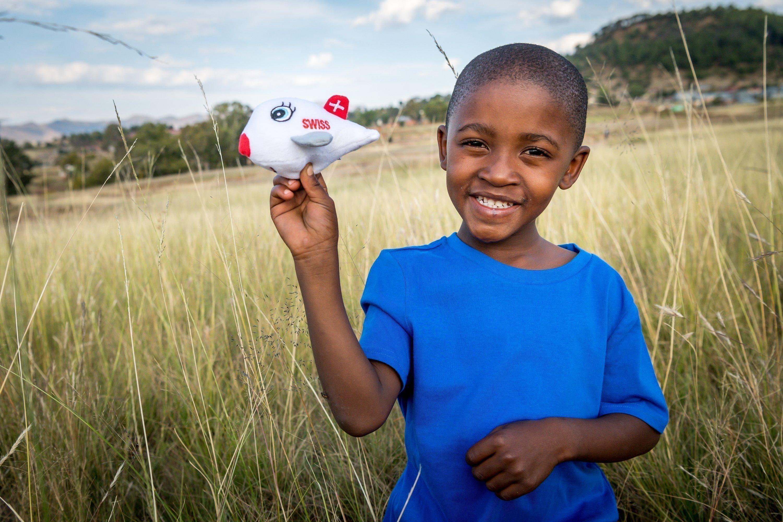 Afrikanischer Junge hält kleines SWISS-Flugzeug in die Kamera.