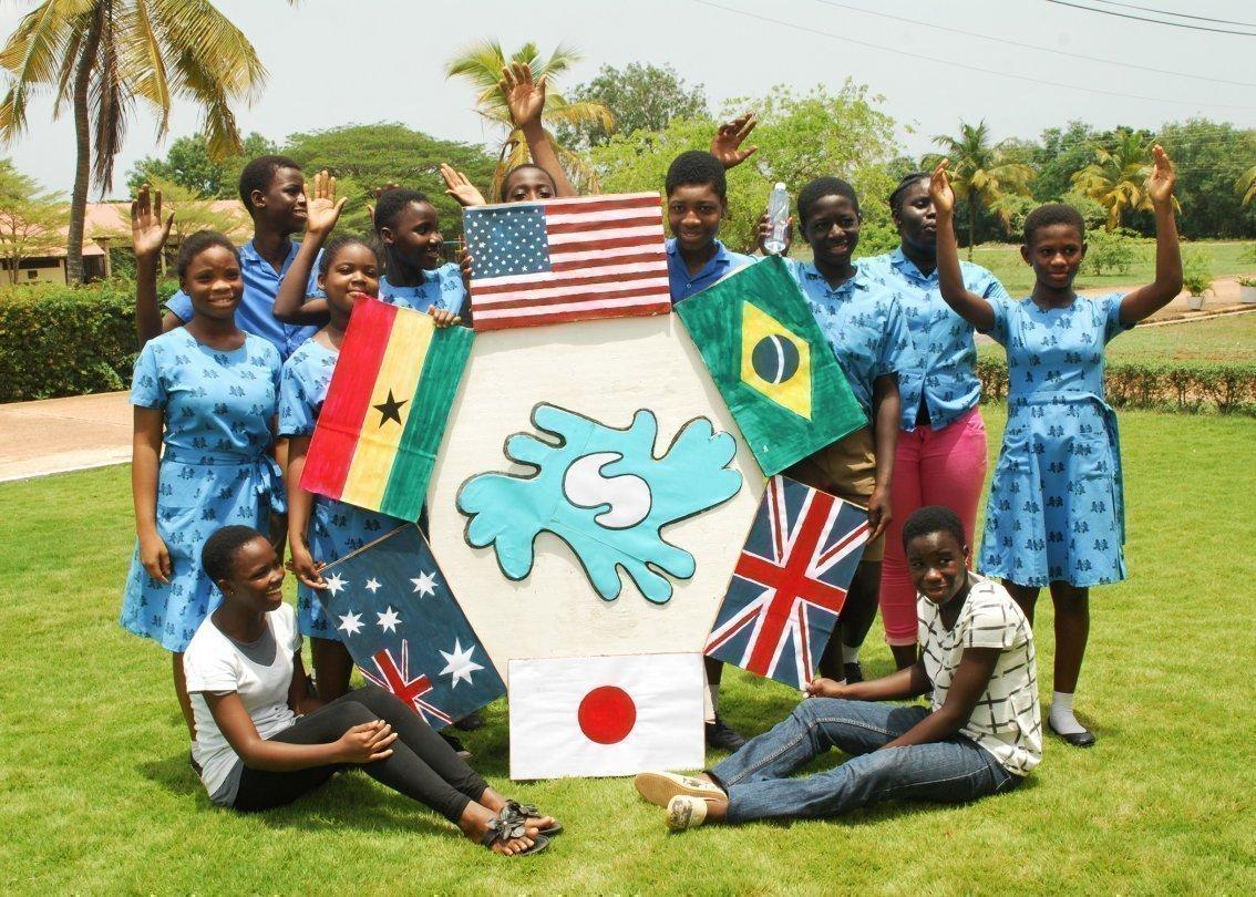 Gruppe von Menschen posieren um eine Skulptur mit Länderflaggen.