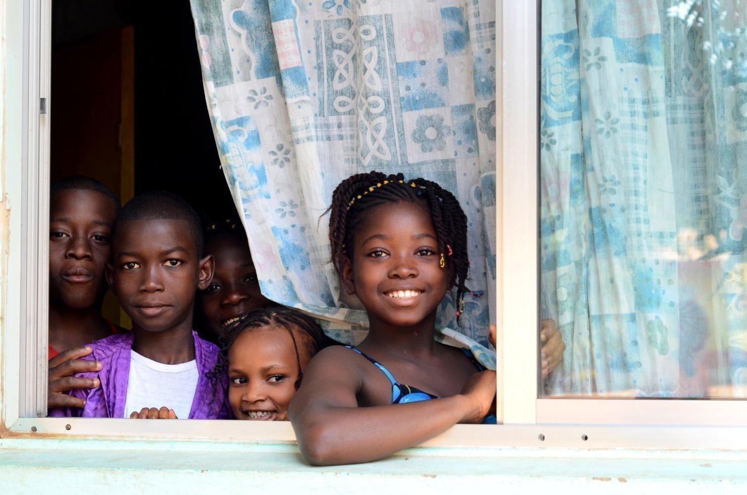 vier Kinder schauen aus einem Fenster heraus.