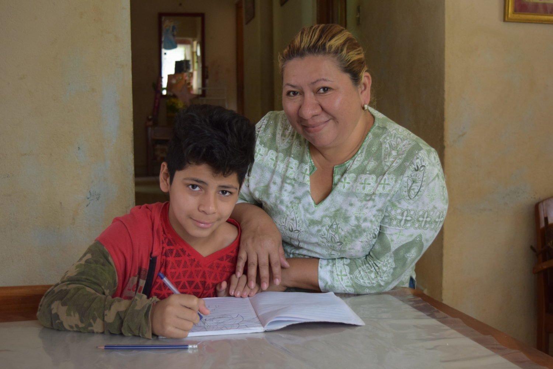 Junge schreibt in ein Heft mit Hilfe einer SOS-Kinderdorf Mutter
