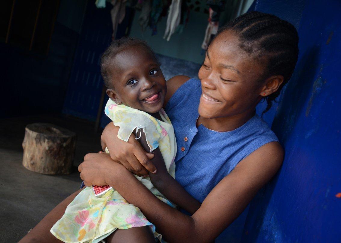Afrikanische SOS-Kinderdorf-Mutter mit lachendem Kind im Arm.
