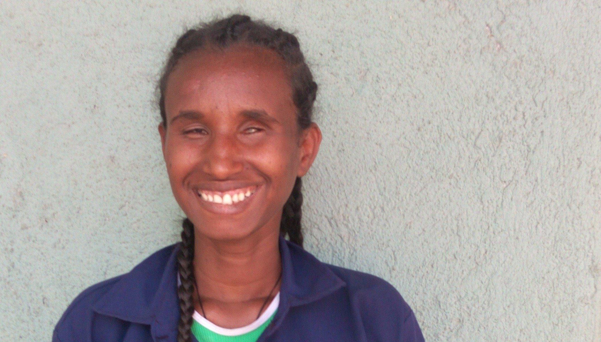 Blinde junge Frau lächelt in die Kamera.