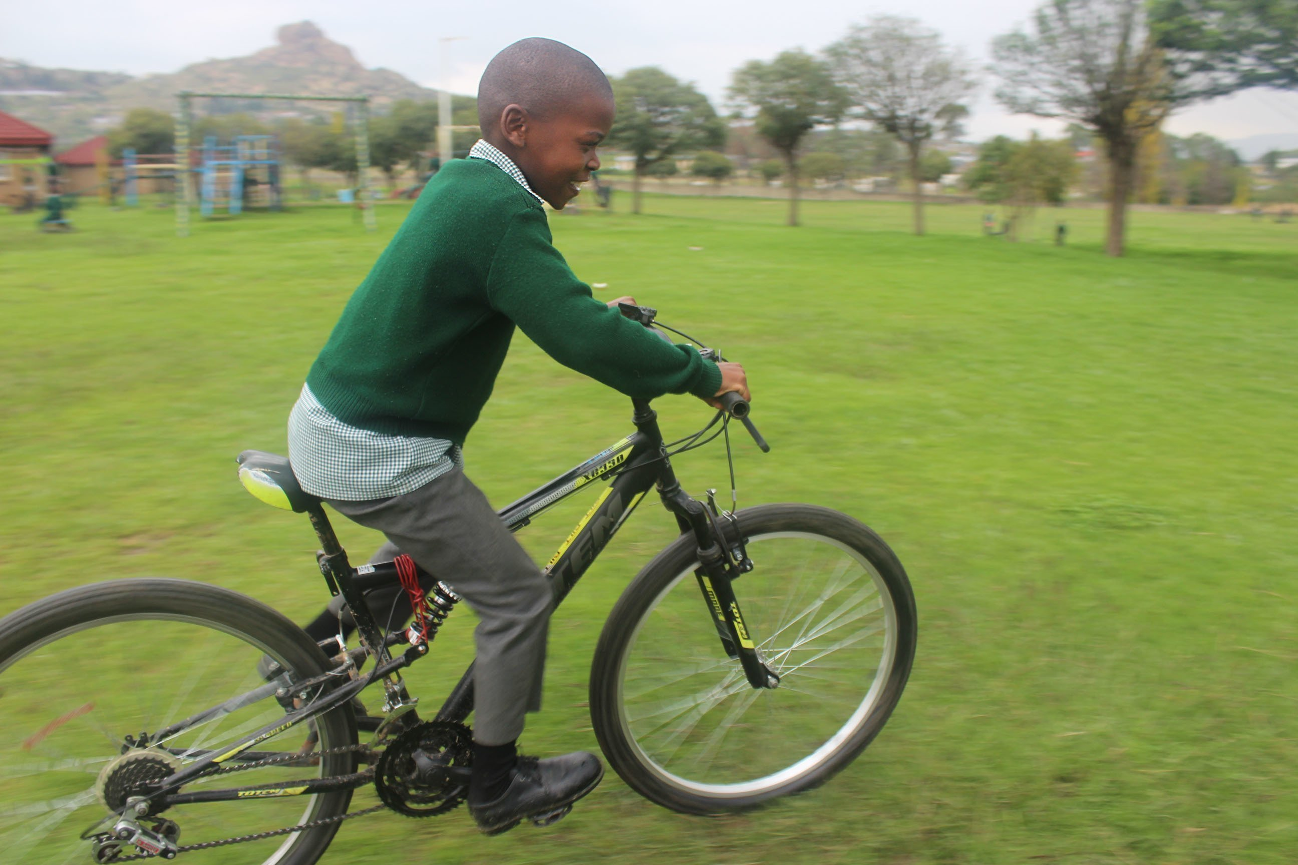 Kind auf einem Fahrrad fährt über einen grünen Rasen.