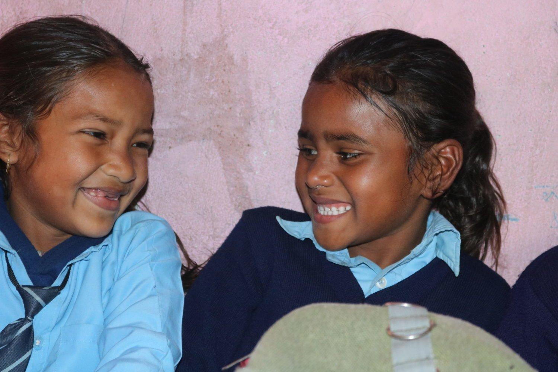 zwei nepalesischen Mädchen lächeln sich an.