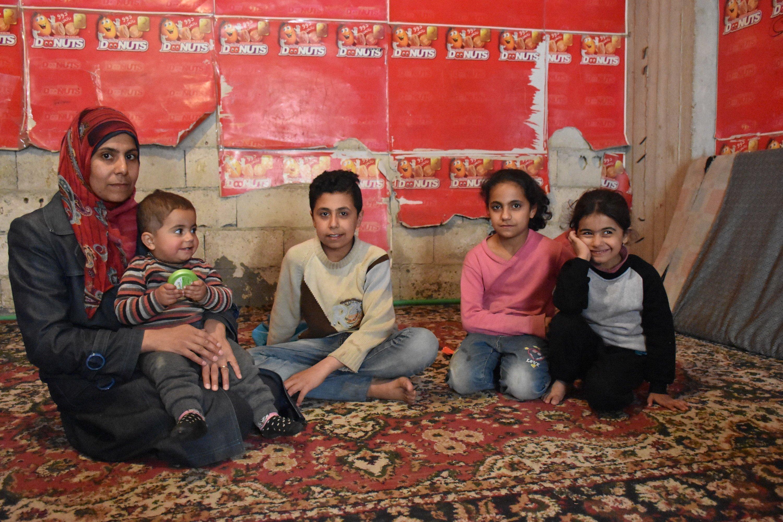 Familie sitzt auf einem Teppich vor einer roten Wand.