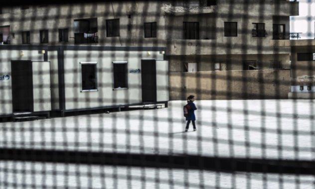 Blick aus einem vergitterten Fenster auf einen Innenhof mit einem Kind.