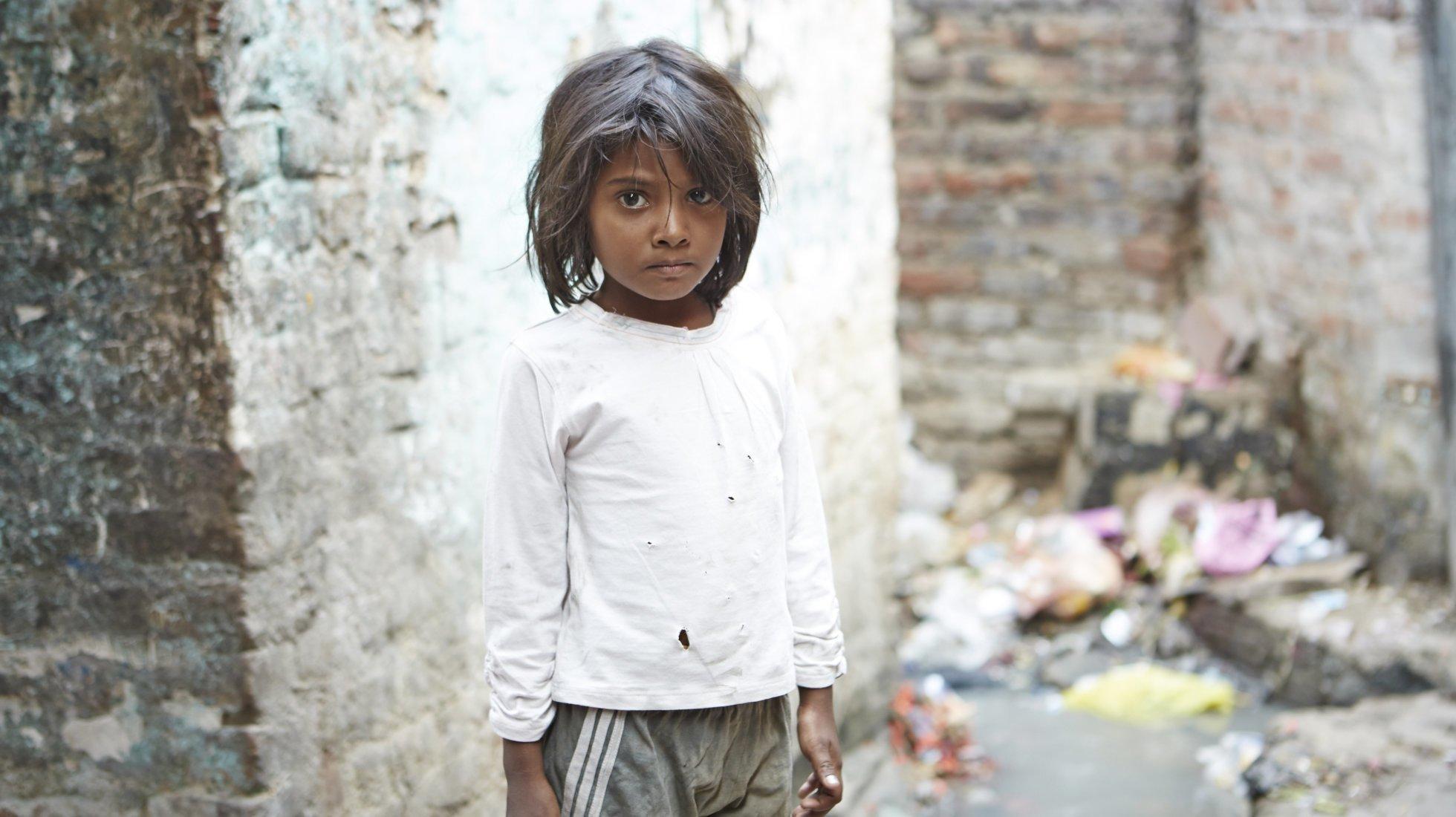 Un bambino è in piedi in un vicolo delle baraccopoli di Delhi. Dietro di lui cumuli di spazzatura.
