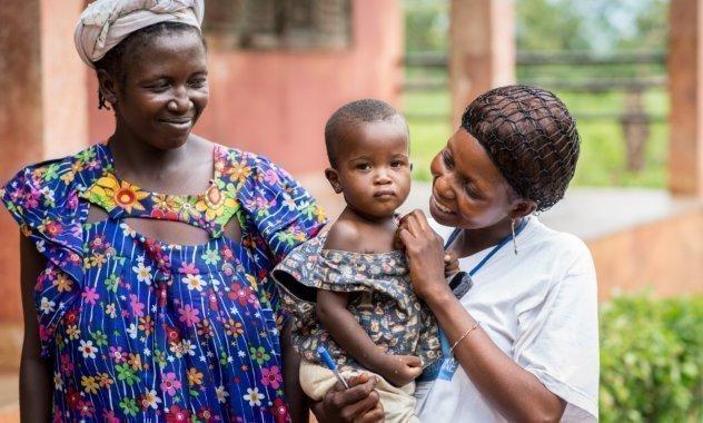 Ein Kind wird von zwei SOS-Kinderdorf Müttern umsorgt.