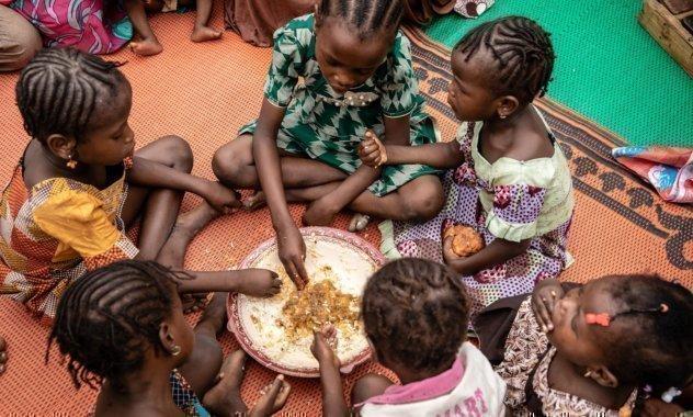 Gruppe von Kindern essen gemeinsam aus einer Schüssel.