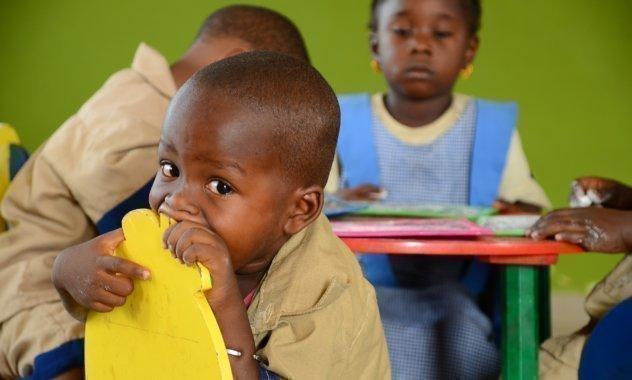 Bambino morde la parte posteriore di una sedia gialla in un SOS Villagio di Bambini.