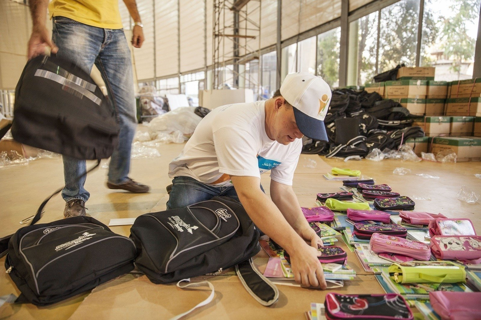 Un bénévole SOS prépare le matériel scolaire à distribuer aux enfants déplacés à Damas.