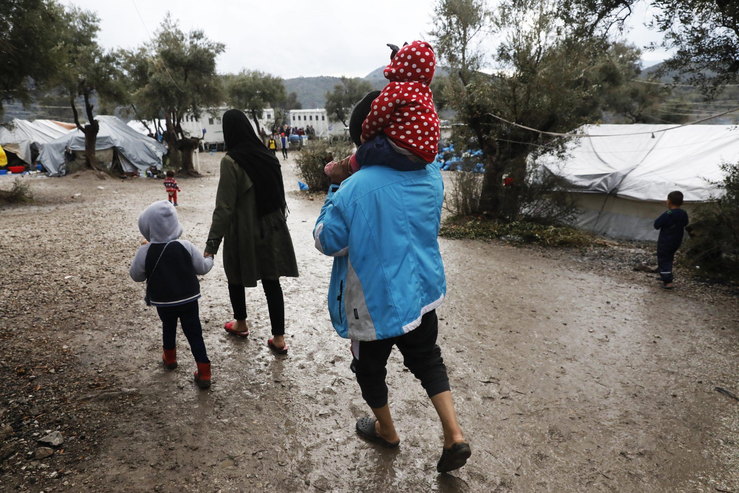 Une famille de quatre personnes marche lentement dans le camp de réfugiés de Mória