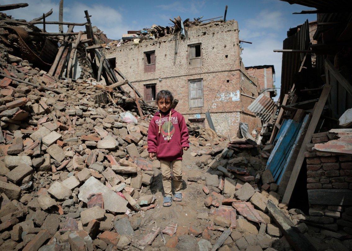 Kind inmitten von Trümmerhaufen.